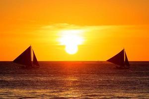 zeilboten bij zonsondergang op een tropische zee. silhouet foto.