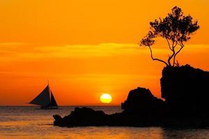 zeilboot bij prachtige zonsondergang boven de tropische zee. silhouet foto. foto
