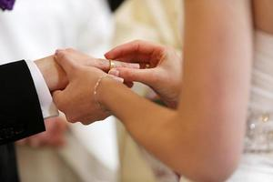 een paar dat geloften en trouwringen uitwisselt foto