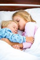klein meisje en jongen slapen op wit bed foto