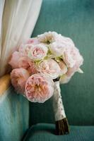boeket van roze pioenrozen gestut op een stoel foto