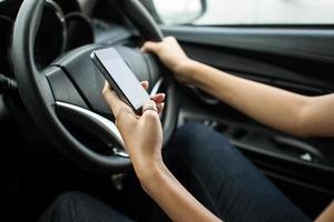 close-up van een vrouwenhand die een tekst verzendt tijdens het rijden foto