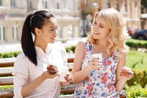 twee vriendinnen in park met koffie en cakejes