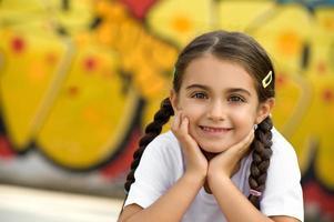lachende schattig klein meisje met handen op gezicht foto