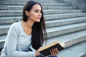 vrouw zittend op de trap van de stad met boek buitenshuis foto