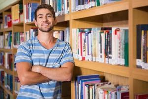 student lachend naar de camera in de bibliotheek