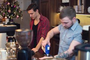 twee hipsters die in een coffeeshop werken en bestellingen schoonmaken
