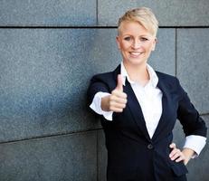 zelfverzekerde zakenvrouw duimen opdagen foto