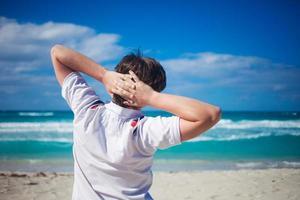 knappe jongeman tegen strand achtergrond, ontspant zijn handen achter foto