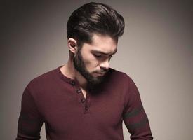 man met een bordeauxrode trui, naar beneden kijkend foto