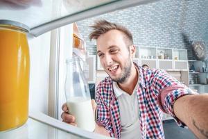 de koelkast controleren. jonge en mannelijke blikken in de koelkast foto