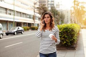 jonge vrouw praten over de mobiele telefoon tijdens het wandelen foto