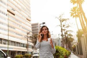 mooie vrouw lopen op stadspalmen laan foto