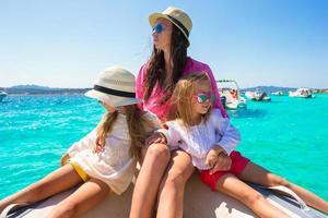jonge moeder met haar schattige kleine meisjes rusten op de boot foto