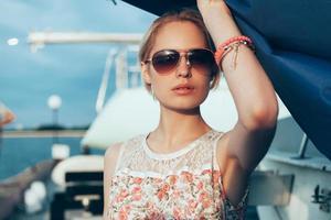 blond meisje in bloem jurk en zonnebril boot zeilen houden foto