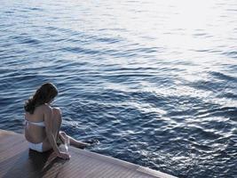 vrouw voet in zee dompelen zittend op de vloer van het jacht foto