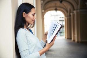 vrouw leesboek buitenshuis foto