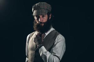 stijlvolle man met baard in formeel pak met pet foto