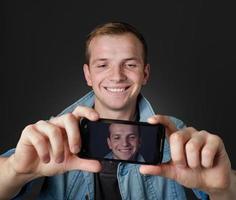 jonge man nam een zelffoto met zijn mobiel. foto