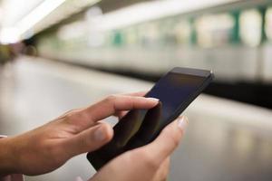 vrouw met behulp van haar mobiele telefoon op metroplatform foto