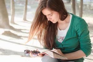 vrouw die een boek leest in het park bij het meer