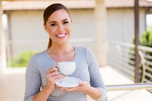 jonge vrouw koffie drinken op balkon foto