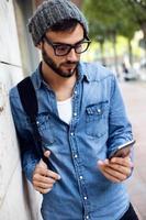 moderne jongeman met mobiele telefoon in de straat. foto