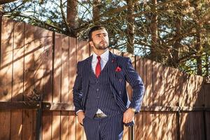 man tegen houten hek in stijlvol pak. foto