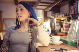 jonge vrouw met blauw haar aan de bar foto