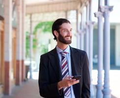 zakenman lachend buitenshuis met mobiele telefoon foto