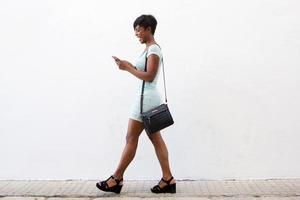 lachende jonge vrouw lopen en kijken naar mobiele telefoon foto