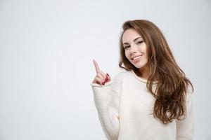 lachende jonge vrouw wijzende vinger omhoog foto