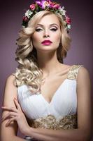 mooi blond meisje in beeld van bruid met bloemen foto
