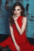 mooie vrouw in rode jurk met op blauwe achtergrond