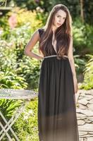vrouw in luxe zwarte jurk poseren in zomertuin.