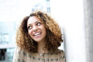 mooie jonge zwarte vrouw die lacht buitenshuis