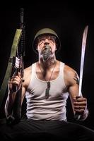 soldaat met granaat in de mond, bril, dog tags, wapens foto