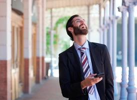 zakenman lachen met mobiele telefoon buitenshuis foto