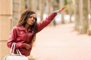 afrikaanse vrouw die een taxi begroet