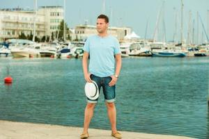 mode portret van knappe man op pier tegen jachten