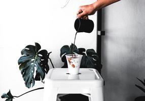 persoon koffie gieten in beker foto