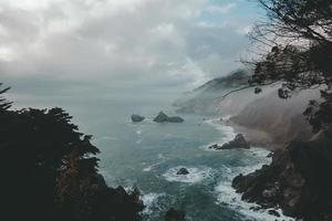 luchtfotografie van de oceaan naast de berg foto