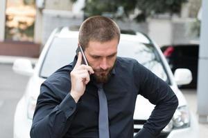 man praten over de telefoon in de buurt van een auto foto