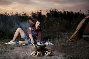 jong koppel knuffelen bij het vuur foto