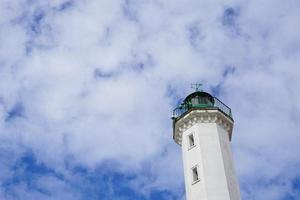 vuurtoren met bewolkte blauwe hemel foto