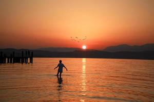 man lopen in de zee onder gouden uur foto