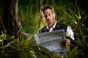 zakenman die financieel nieuws in de jungle leest foto