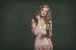 vintage mode vrouw met oude parfumfles. roze vest dragen. foto