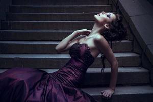 mooie vrouw in een paarse jurk voor fotografie foto