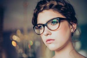 portret van een jonge vrouw die een bril draagt foto